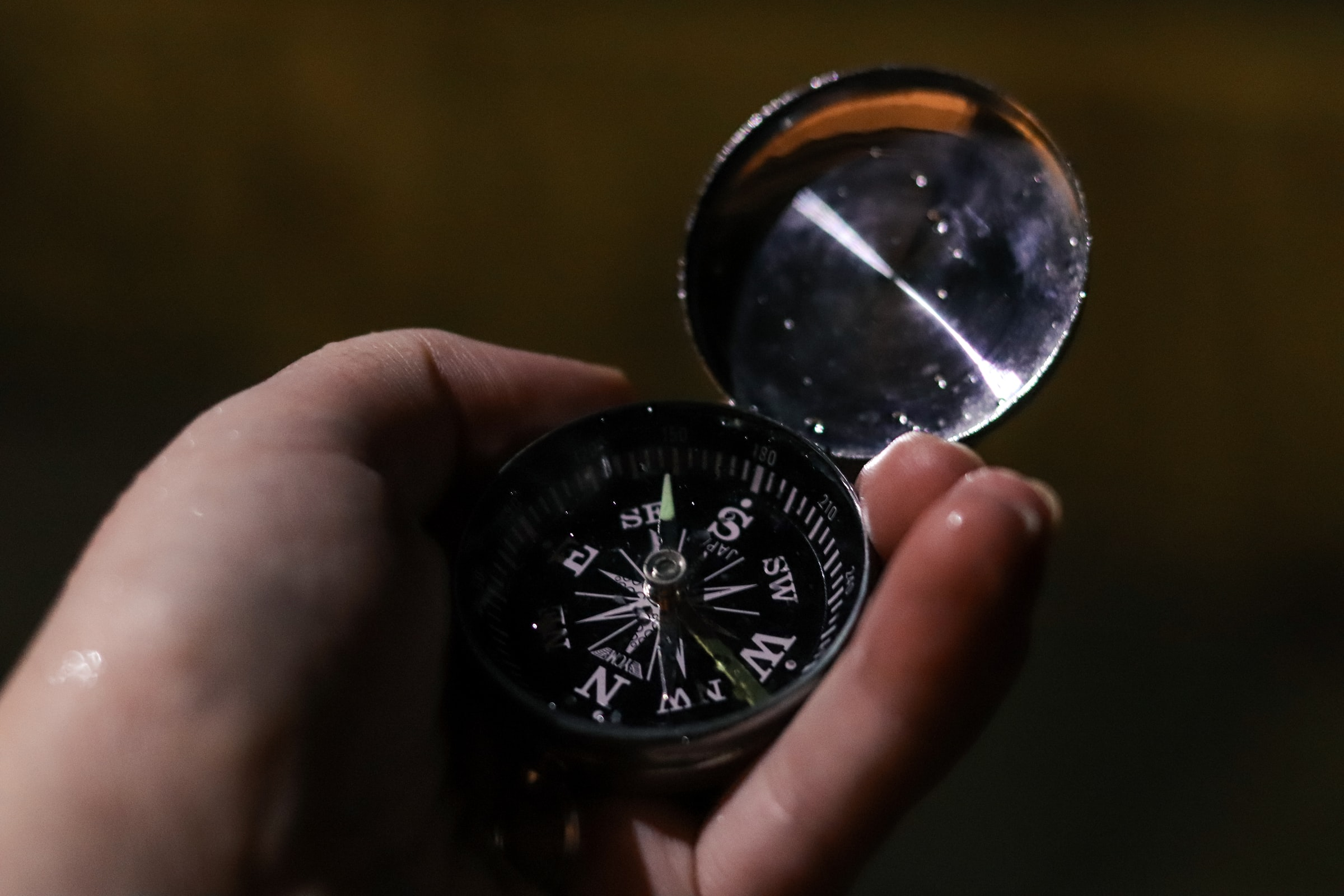 Closeup of hand holding compass.