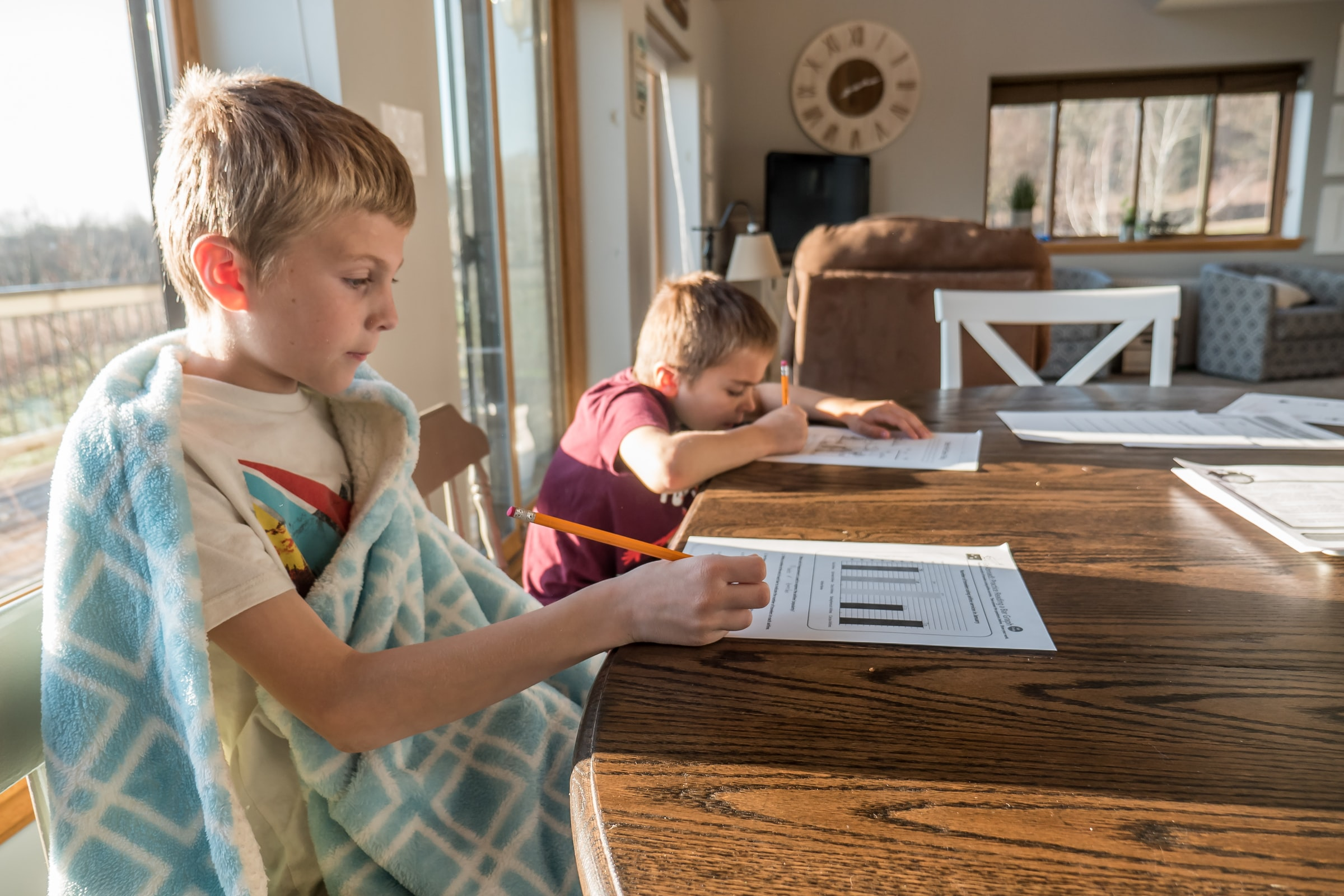 two children doing homework at table